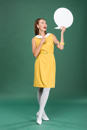 beautiful stylish woman in yellow dress pointing with finger and holding speech bubble on green background