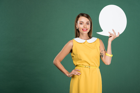 beautiful smiling woman in yellow dress looking at camera and holding speech bubble isolated on green 版權商用圖片
