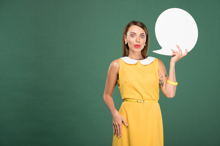 beautiful surprised woman in yellow dress holding speech bubble isolated on green with copy space 版權商用圖片
