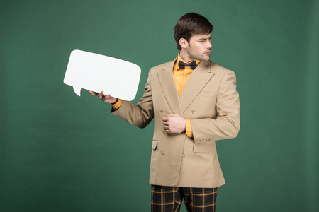 handsome man in vintage clothes holding speech bubble and looking away isolated on green