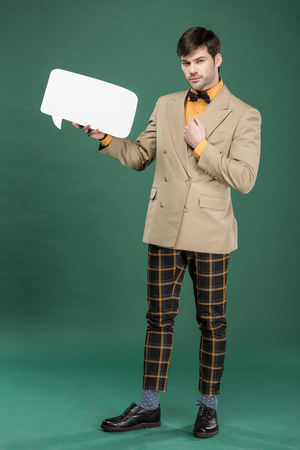 handsome man in vintage clothes holding speech bubble on green background Reklamní fotografie
