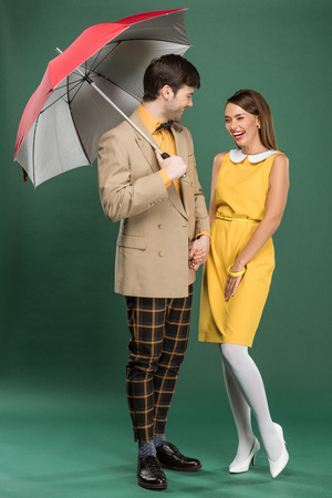 beautiful laughing couple in vintage clothes posing with umbrella on green background