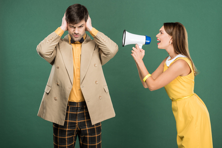 man in vintage clothes covering ears with hands while angry woman yelling in loudspeaker isolated on green