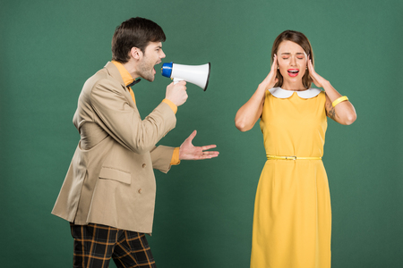 woman in vintage clothes covering ears with hands while angry man yelling in loudspeaker isolated on green 版權商用圖片