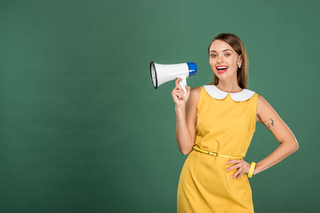 beautiful stylish woman in yellow dress shouting in loudspeaker isolated on green with copy space