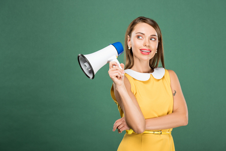 beautiful stylish woman in yellow dress holding loudspeaker isolated on green with copy space