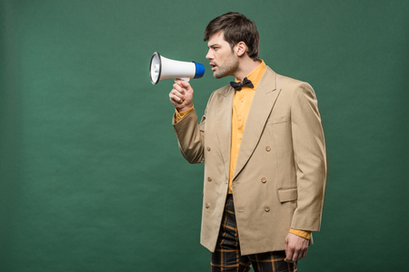handsome man in vintage clothes talking in loudspeaker isolated on green with copy space Reklamní fotografie