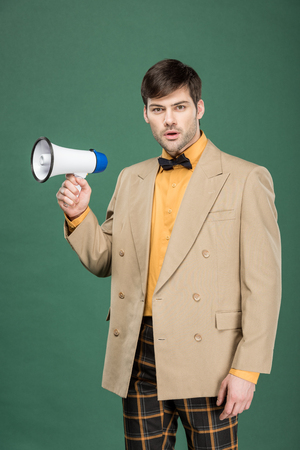 handsome man in vintage clothes holding loudspeaker and looking at camera isolated on green