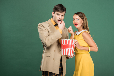 beautiful couple in vintage clothes eating popcorn while watching movie isolated on green 版權商用圖片