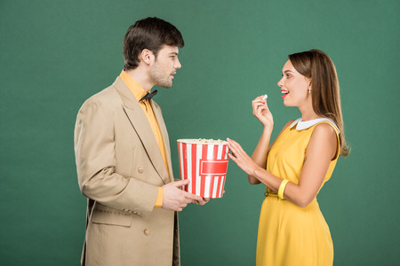 beautiful couple in vintage clothes eating popcorn and looking at each other isolated on green Reklamní fotografie