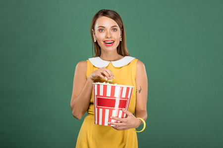beautiful woman holding bucket of popcorn and looking at camera isolated on green