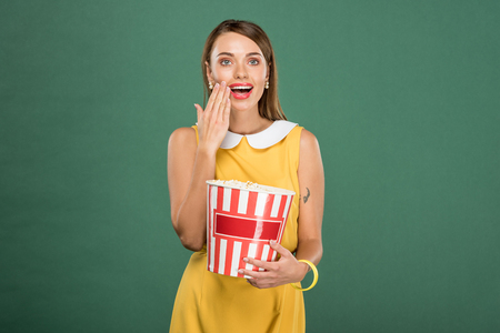beautiful surprised woman holding bucket of popcorn and covering mouth with hand isolated on green