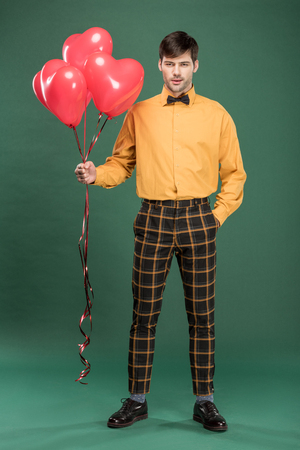 handsome man in vintage clothes with heart shaped balloons on green background Фото со стока
