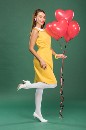 beautiful woman holding heart shaped balloons and looking at camera on green background 版權商用圖片