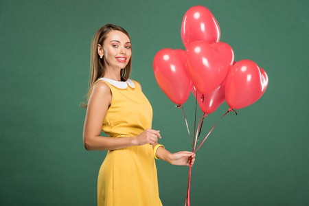 beautiful woman holding heart shaped balloons and looking at camera isolated on green
