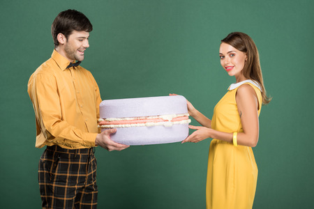 beautiful smiling couple in vintage clothes holding macaroon model isolated on green 版權商用圖片