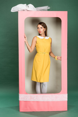 beautiful stylish woman in yellow dress posing in decorative pink box with bow on green background Reklamní fotografie