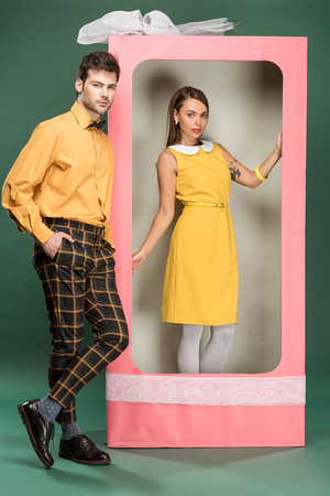 beautiful woman posing in decorative pink box with bow while handsome man in vintage clothes looking away on green background
