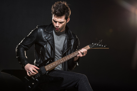handsome rocker in leather jacket playing electric guitar on black background