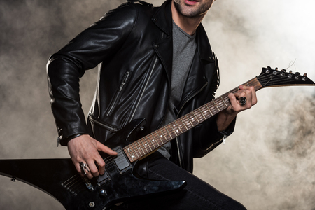 cropped view of rocker in leather jacket playing electric guitar on smoky background