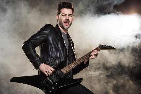 handsome rocker in leather jacket playing electric guitar on smoky background 版權商用圖片