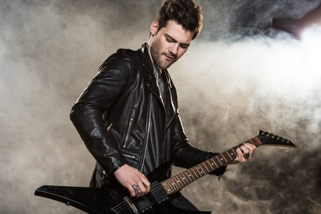 handsome rocker in leather jacket playing electric guitar on smoky background Stock Photo