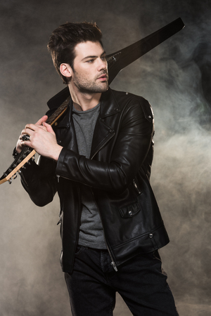handsome rocker holding electric guitar and looking away on smoky background