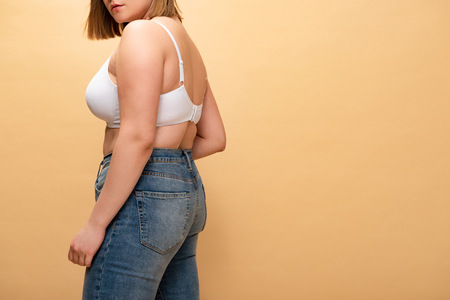 cropped view of overweight girl in blue jeans and bra isolated on beige, body positivity concept