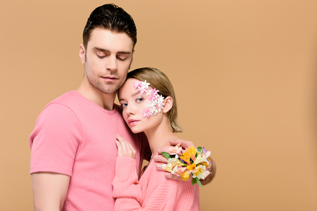 handsome man with closed eyes embracing attractive girlfriend with flowers on face isolated on beige