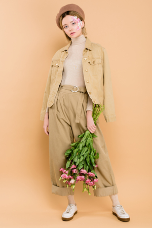 stylish girl in beret holding bouquet with eustoma flowers isolated on beige 写真素材
