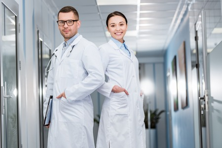 Confident doctors in white coats standing with hands in pockets