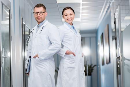 Confident doctors in white coats standing with hands in pockets 版權商用圖片