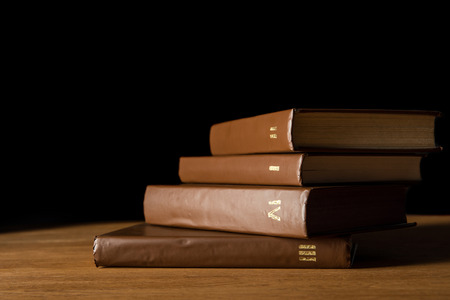 selective focus of brown leather books on wooden table isolated on black Stock Photo