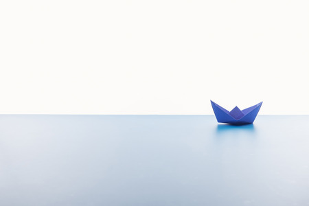 Blue paper boat on light surface on white background