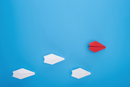 Flat lay with white and red paper planes on blue Imagens