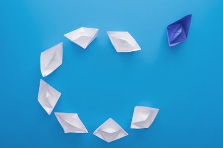Flat lay with white and blue paper boats on blue 免版税图像
