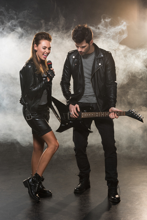 beautiful woman in leather jacket singing while man playing electric guitar on smoky background