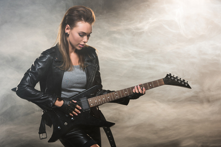 beautiful woman in leather jacket playing electric guitar on smoky background
