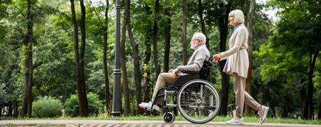 senior woman with husband in wheelchair walking in park