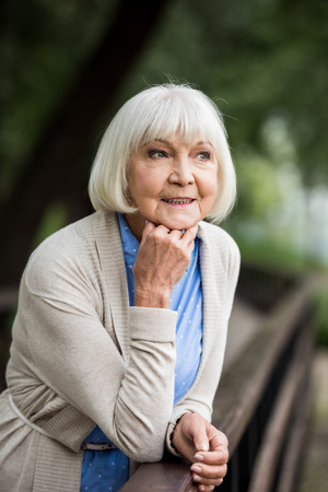 selective focus of senior woman leaning on wooden bridge railing and looking away