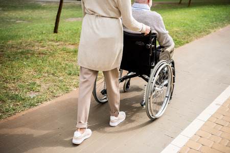 cropped view of senior woman carrying husband in wheelchair while walking in park