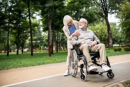 nice senior woman with husband in wheelchair in park Stok Fotoğraf