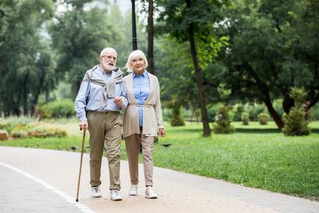 happy stylish senior couple enjoying walking in park