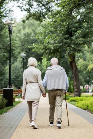 back view of stylish senior couple enjoying walking in park Stock fotó