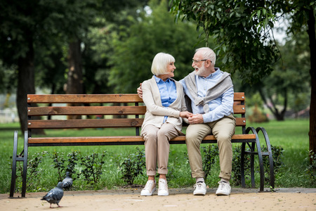 senior couple talking and smiling while sitting on wooden bench in park