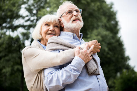 happy senior couple embracing and smiling in park