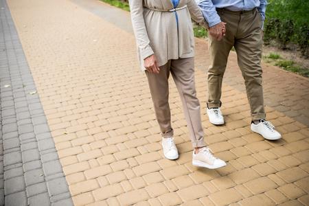 cropped view of senior couple walking across paved sidewalk in park Stock fotó