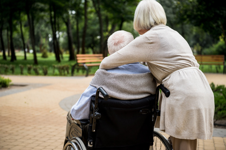 back view of senior woman with husband in wheelchair in park
