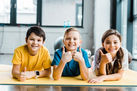 Laughing kids posing on fitness mat with thumbs up