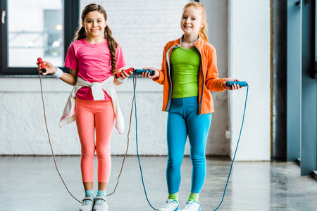 Adorable children training with skipping ropes in gym